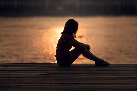 60343150 - Sad Woman Silhouette Worried At Sunset
